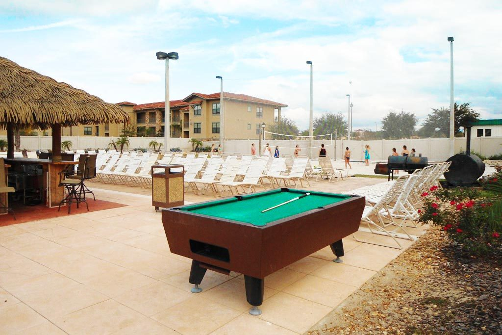 Tiki bar, pool table and sand volleyball court